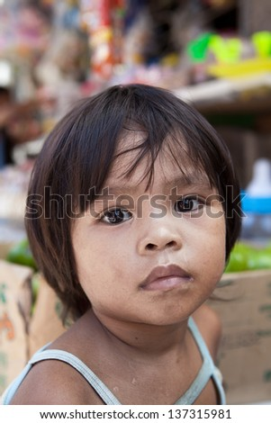 Asian child from impoverished area - natural portrait by a local market in the Philippines. - stock photo