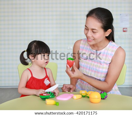 Asian Child girl and mother playing plastic fruits at the Kid room - stock photo