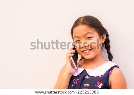 asian child girl holding smiling face  hold smart phone,touch screen, tab, on gray wall background.