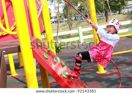 Asian Child girl jungle gym in playground. Outdoor park - stock photo