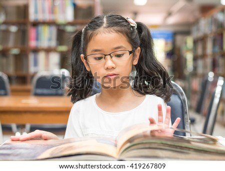 Asian child girl w/ eyeglasses reading book school background: Lovely cute young happy smart student kid opening flipping book in archive resource collection room: National library lover month week - stock photo