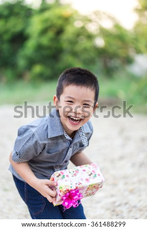 Asian child holding Christmas gift box in hand with smiling face
