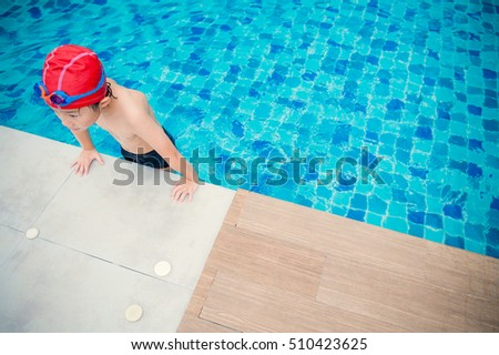 Asian child is in a swimming pool .