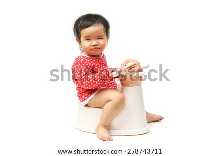 Asian child on potty play - learning to use toilet - stock photo