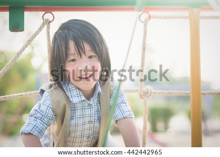Asian child playing on playground in summer outdoor park