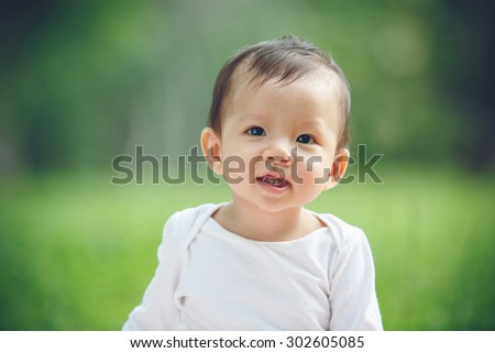 Asian child portrait in garden (soft focus on the eyes) - stock photo