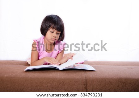 Asian Child Read a Book on bed