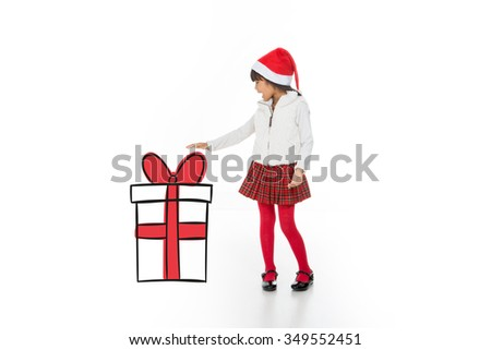 asian child showing her xmas gift with a surprise expression - stock photo