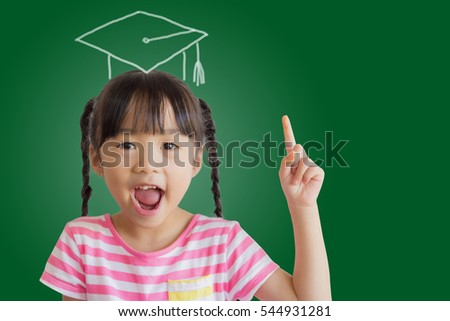 asian child smile and point up on the blackboard with a picture of graduation cap on her head