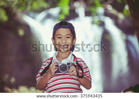 Asian child smiling and holding camera on blurred waterfall background. Handsome boy looking at camera in nature. Outdoors portrait. Vintage picture style. - stock photo