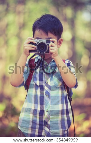 Asian child taking photos by professional digital camera on blurred background. Photo in retro style. Smart boy in nature. Outdoors portrait. - stock photo