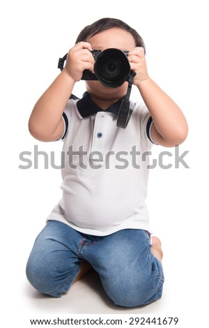 Asian Child using a camera. Little Boy holding camera and taking photo. isolated - stock photo