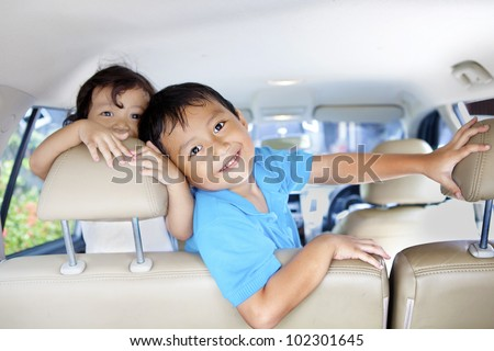 Asian children ready for a road trip posing in car - stock photo