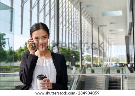 asian chinese businesswoman office worker communicating with mobile phone on coffee break - stock photo