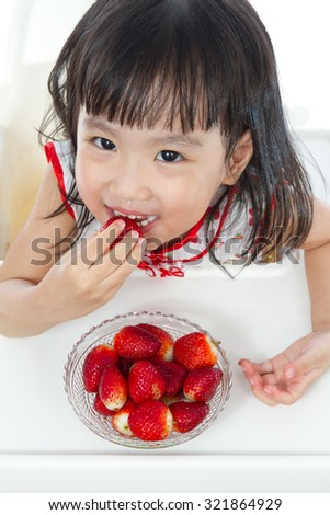 Asian Chinese children eating strawberries in plain white background. - stock photo