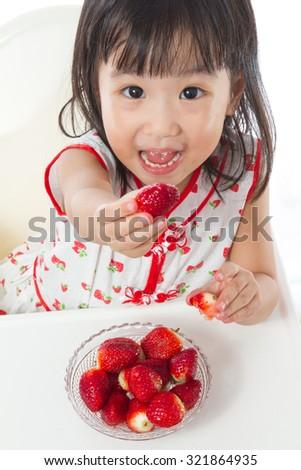 Asian Chinese children eating strawberries in plain white background. - stock photo