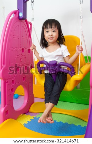 Asian Chinese children playing on swing at indoor playground. - stock photo
