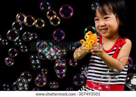 Asian Chinese children Playing Soap Bubbles in black background indoor. - stock photo