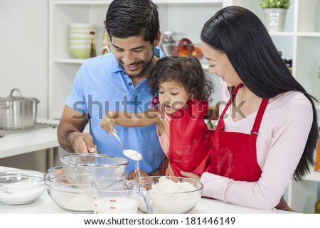 Asian Chinese family, man & woman parents and young girl child daughter cooking, baking, making cakes in home kitchen - stock photo