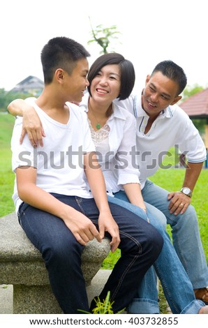 Asian Chinese Family Relaxing In Park