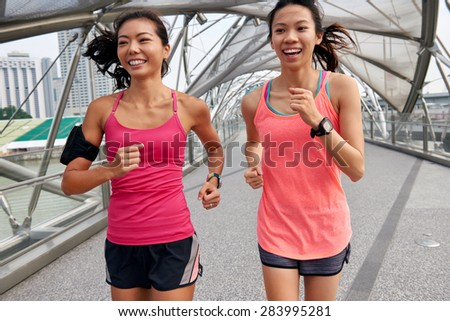 asian chinese happy women enjoying a run together for morning outdoor workout - stock photo
