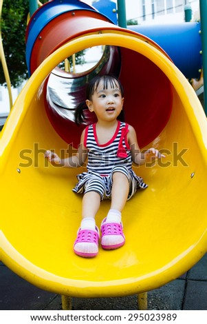 Asian Chinese little girl sliding on playground outdoor. - stock photo