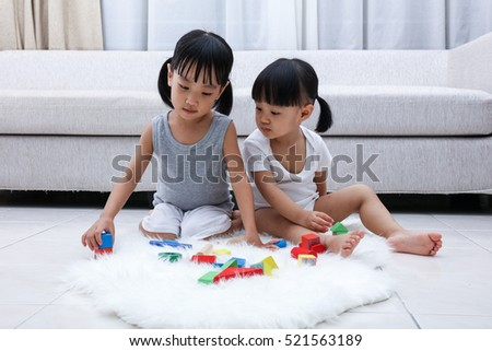 Asian Chinese little sisters playing blocks on the floor in the living room at home.