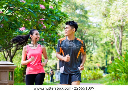 Asian Chinese man and woman jogging in city park - stock photo