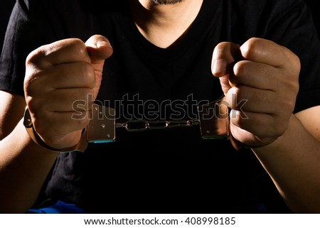 Asian Chinese Man with handcuffs in isolated Black Background - stock photo