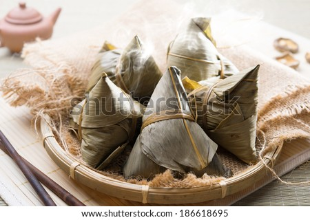 Asian Chinese rice dumplings on basket, tea at background. - stock photo