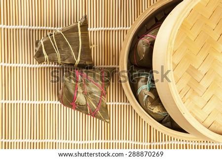 Asian Chinese rice dumplings on basket, tea at background. - stock photo