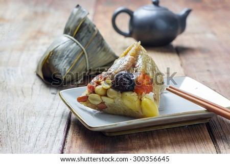 Asian Chinese rice dumplings or zongzi with tea on wood - stock photo
