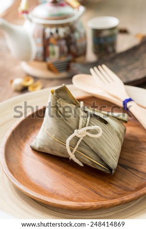 Asian Chinese rice dumplings or zongzi with tea on wooden background - stock photo