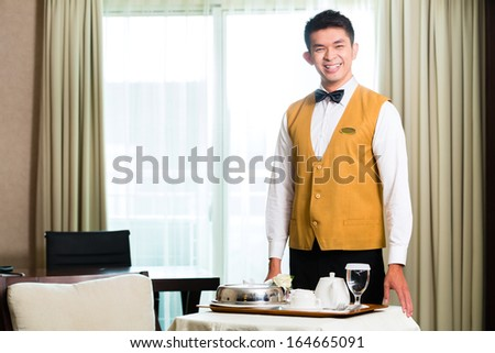 Asian Chinese room service waiter or steward serving guests food in a grand or luxury hotel room  - stock photo