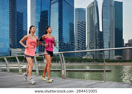 asian chinese sporty running women working out jogging outdoors along urban city harbor sidewalk morning - stock photo