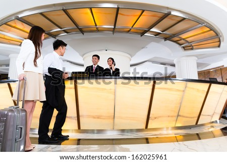 Asian Chinese woman and man arriving at front desk or reception of luxury hotel in business clothes with trolley  - stock photo
