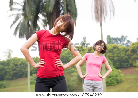Asian Chinese woman workout outdoor, stretching - stock photo