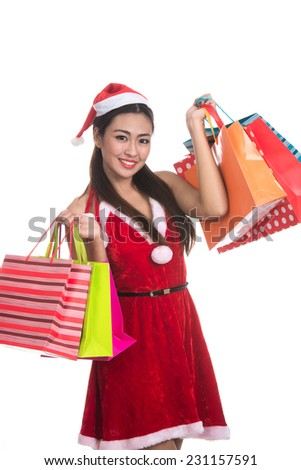 Asian Christmas girl hold shopping bags,sale, gifts, christmas, x-mas concept - smiling woman in red shirt and santa helper hat with shopping bags,isolated on white background