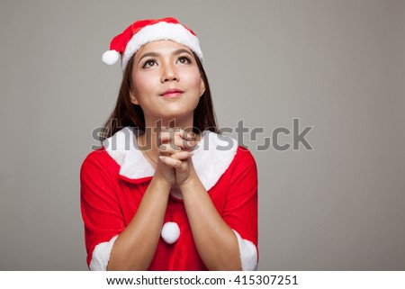 Asian Christmas girl with Santa Claus clothes is praying on gray background