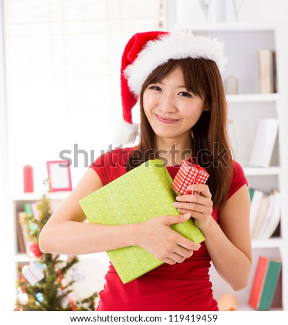 Asian Christmas woman with gift, indoor / inside house.