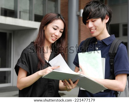 Asian college couple student standing holding book on campus - stock photo