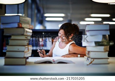 Asian college student girl sitting at the library desk and writing something in his note pad, young woman reading a book preparing to the exams in high school, night before exam in university - stock photo