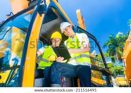 Asian construction machinery driver discussing with foreman blueprints  or tablet computer of building site  - stock photo