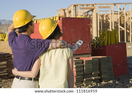 Asian couple at construction site - stock photo