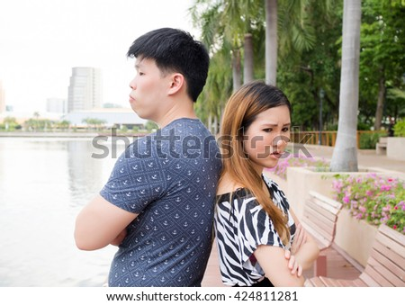 Asian couple being mad at each other in the park - stock photo