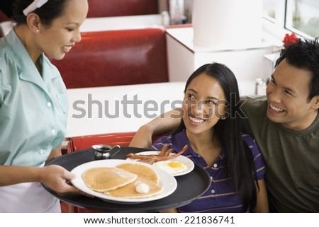 Asian couple being served food at diner - stock photo