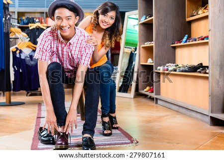 Asian couple buying shoes in store or shop - stock photo