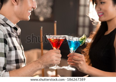 Asian couple clinking their glasses in the bar