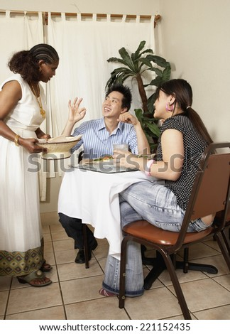 Asian couple complimenting owner of restaurant - stock photo