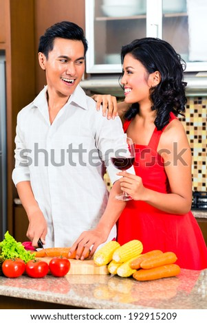 Asian couple cooking and cutting vegetables in domestic kitchen, drinking red wine